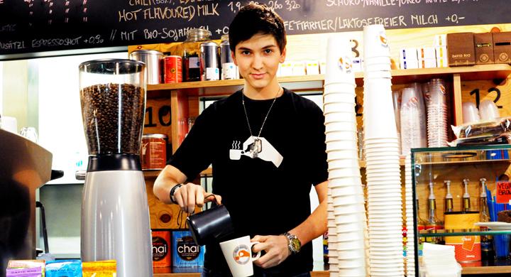 Jugendlicher hinter einer Theke in einem Cafe