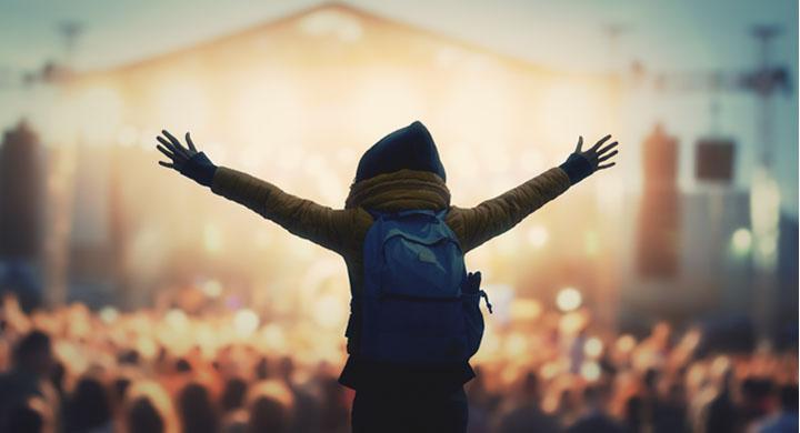 Jugendlicher mit ausgestreckten Armen vor einer Konzertbühne auf einem Festival