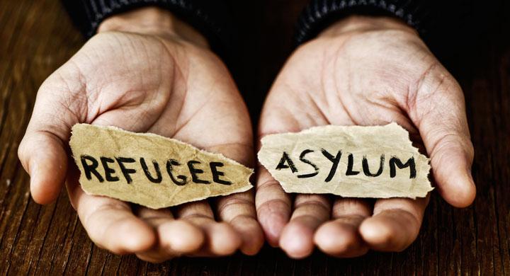 Hände die Zettel mit den Worten Refugee und Asylum halten