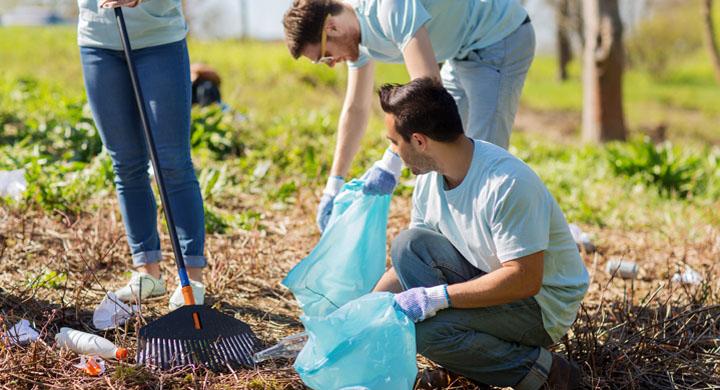 Jugendliche sammeln Müll in der NAtur ein.