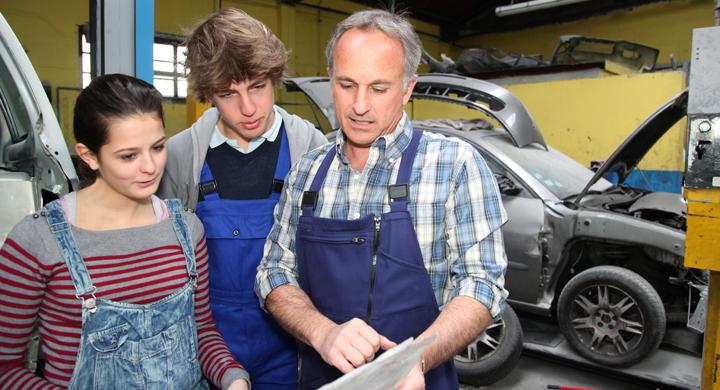 2 Jugendliche in einer Autowerkstatt erhalten von einen Ausbildner eine erklärung