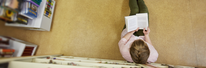 Jugendliche sitzt am Boden in einer Bibliothek und liest ein Buch