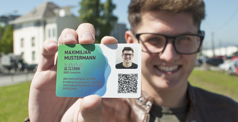 Junger Mann streckt neue aha card in die Kamera