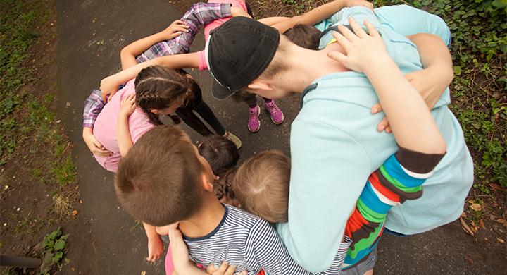 Junge Leute stehen im Kreis zusammen und umarmen sich