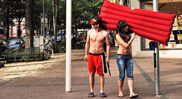 Ein junges Päärchen steht am Straßenrand, mit einer roten Luftmatratze in der Hand.